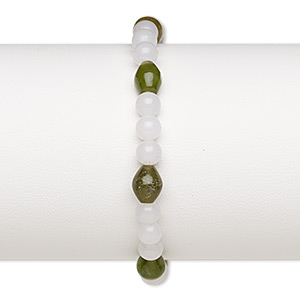 bracelet, stretch, dark olive new jade (natural) and acrylic, white, 5-6mm round and 8x6mm-9x7mm oval, 7 inches. sold individually.