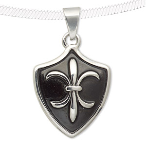 pendant, epoxy and stainless steel, black, 30x24mm shield with fleur-de-lis design. sold individually.